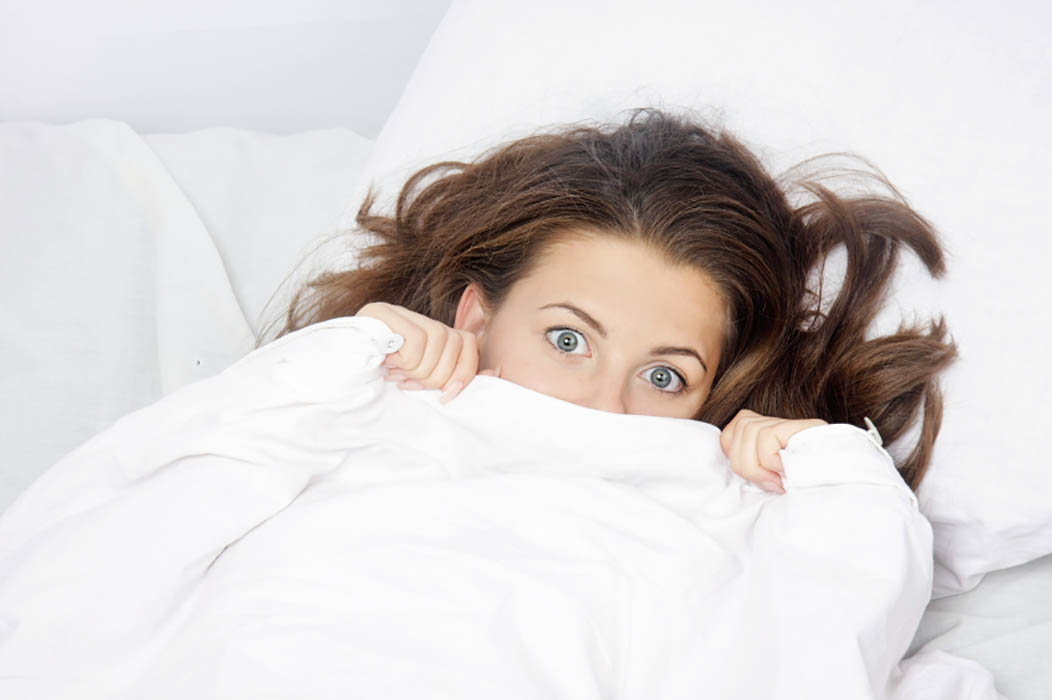 young scared woman in bed